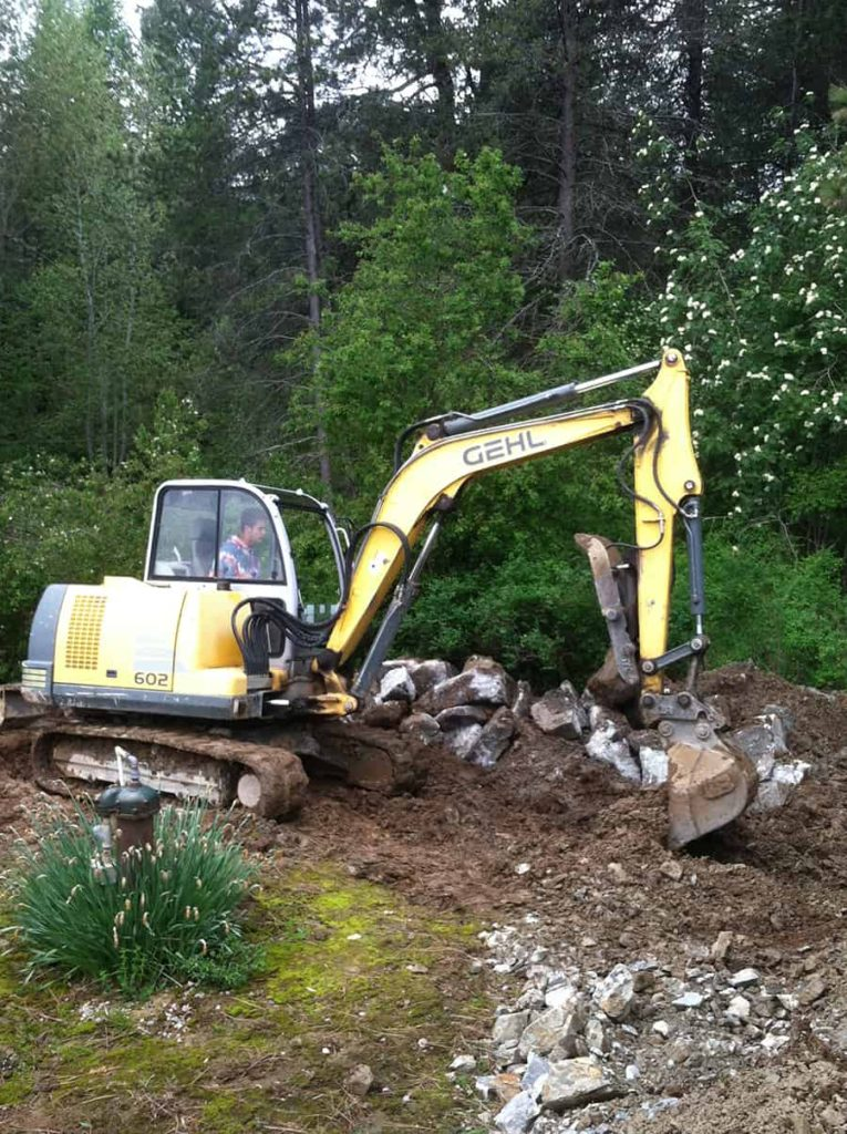 four-seasons-excavating-excavator-rocks-woods